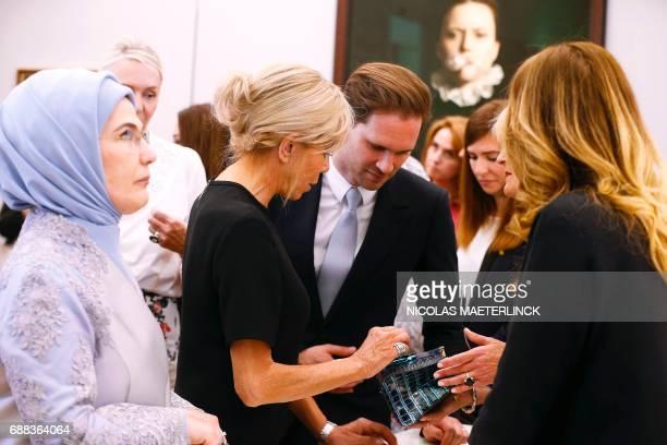 First Lady of Turkey Emine Gulbaran Erdogan First Lady of France Brigitte Macron and First Gentleman of Luxembourg Gauthier Destenay are pictured...