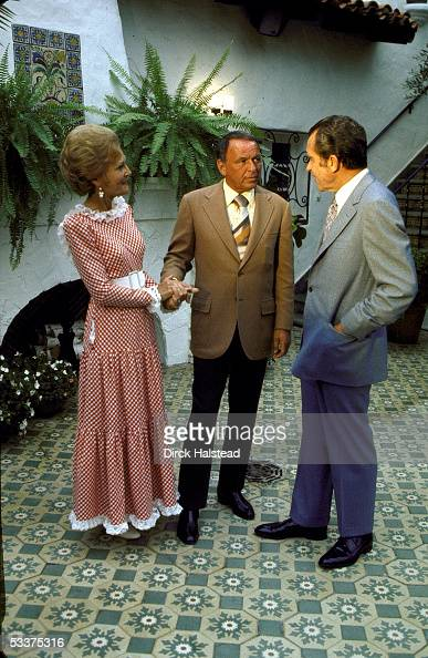 First Lady Pat Nixon entertainer Frank Sinatra President Richard Nixon chatting during a GOP celebrity fundraising event at Nixon's home