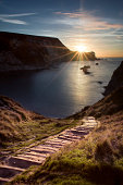 An autumnal sunrise at Man oWar bay; an open coastline that was fashioned from two beaches that the sea joined together, leaving Portland Stone outlines. A Chalk headland marks the point at which the