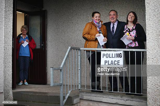 First Minister Alex Salmond stands with first time voters Natasha McDonald 18 and Lia Pirie 28 at a polling station on September 18 2014 in Strichen...