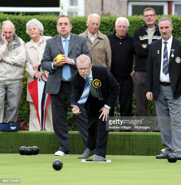 First Minister Alex Salmond waits for his shot while SNP candidate for Glasgow East John Mason plays a shot during a game of bowls while visiting...