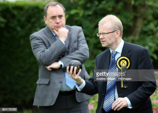 First Minister Alex Salmond with SNP candidate for Glasgow East John Mason who plays a shot during a game of bowls while visiting Garrowhill Bowling...