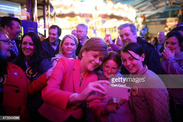 First Minister and leader of the SNP Nicola Sturgeon takes a selfie with supporters during a visit to a theme park while campaigning on May 3 2015 in...