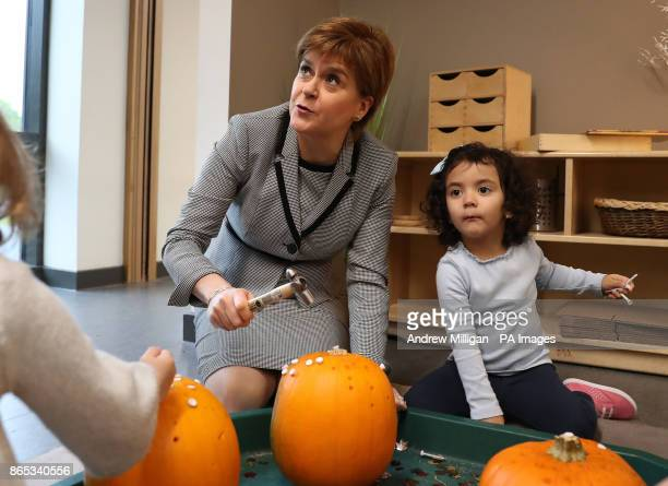 First Minister Nicola Sturgeon helps hammer golf tees into a pumpkin during a visit to Tower View Nursery in Glasgow as she launches a childcare...