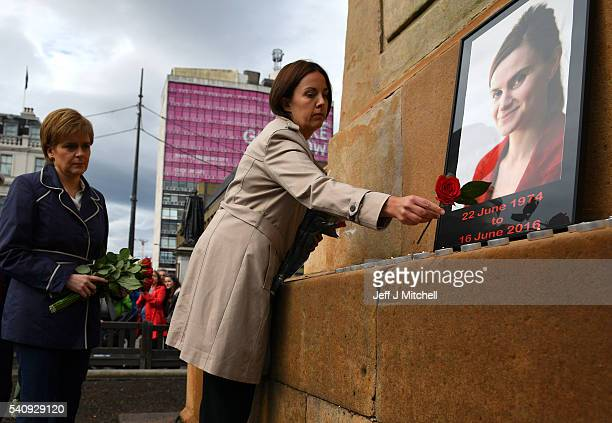 First Minister of Scotland Nicola Sturgeon and Leader of Scottish Labour party Kezia Dugdale place roses near the photograph of Labour MP Jo Cox...