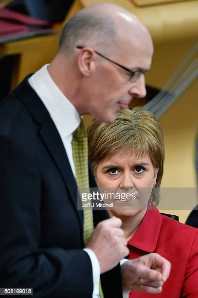 First Minister of Scotland Nicola Sturgeon listens to Finance Secretary John Swinney as he announces his draft budget which is being debated for the...