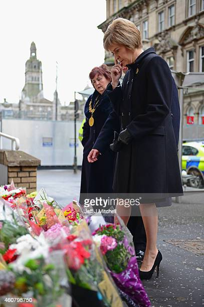 First Minister of Scotland Nicola Sturgeon looks at flowers left near to the scene of yesterday's bin lorry crash on December 23 2014 in Glasgow...