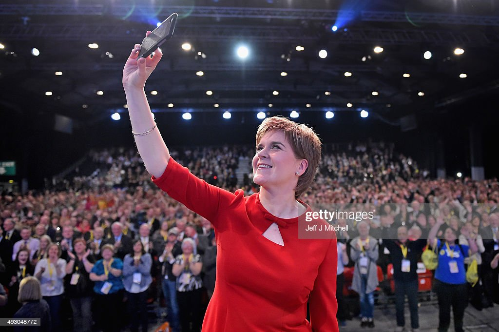 First Minister of Scotland Nicola Sturgeon takes a selfie on stage following her keynote speech at the 81st annual SNP conference at the Aberdeen Exhibition and Conference Centre on October 17, 2015 in Aberdeen, Scotland. During her address to delegates, Nicola Sturgeon announced a pledge to build a new network of NHS treatment centres and more financial support for carers if the SNP wins next year's Holyrood elections.