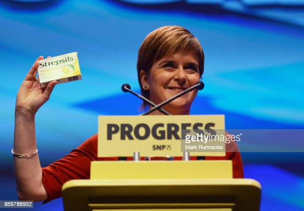 First Minister SNP Leader Nicola Sturgeon waves a packet of Strepsils from the stage as she makes her keynote speech at The SNP Autumn Conference...