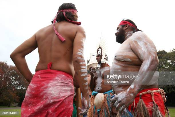 First Nation men dressed in traditional attire prepare for a ceremonial performance at Government House on June 28 2017 in Sydney Australia The flags...