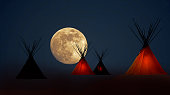 First Nation teepee camp under full moons howing a dim light inside some of the teepees.