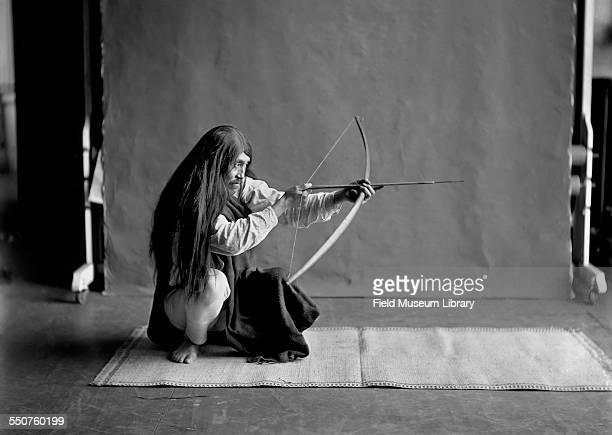 First Nations Kwakiutl man Bob Harris wearing a long hair wig shooting a bow and arrow at the Louisiana Purchase Exposition St Louis Missouri June 6...