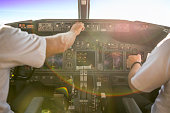 First officer is piloting an aircraft, while captain is setting up heading on main control panel. They are just after takeoff heading against sun. Pilots are sitting in commercial airplane Boeing 737-