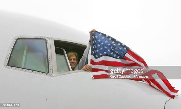 First Officer TJ Mearsheimer flies a US flag from the cockpit window of Continental Airlines flight CO28 after it arrived at London's Heathrow...
