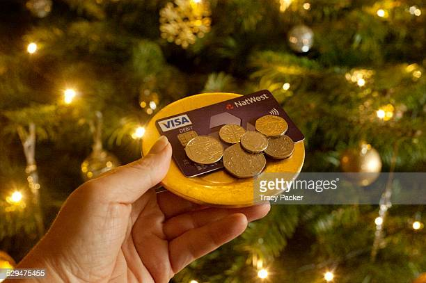 First person perspective showing payment being made with a debit card a cash tip against a festive backdrop of a decorated Christmas Tree