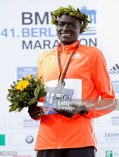 First place winner and new world record holder Dennis Kimetto of Kenya poses on the podium after the 41th BMW Berlin Marathon on September 28 2014 in...