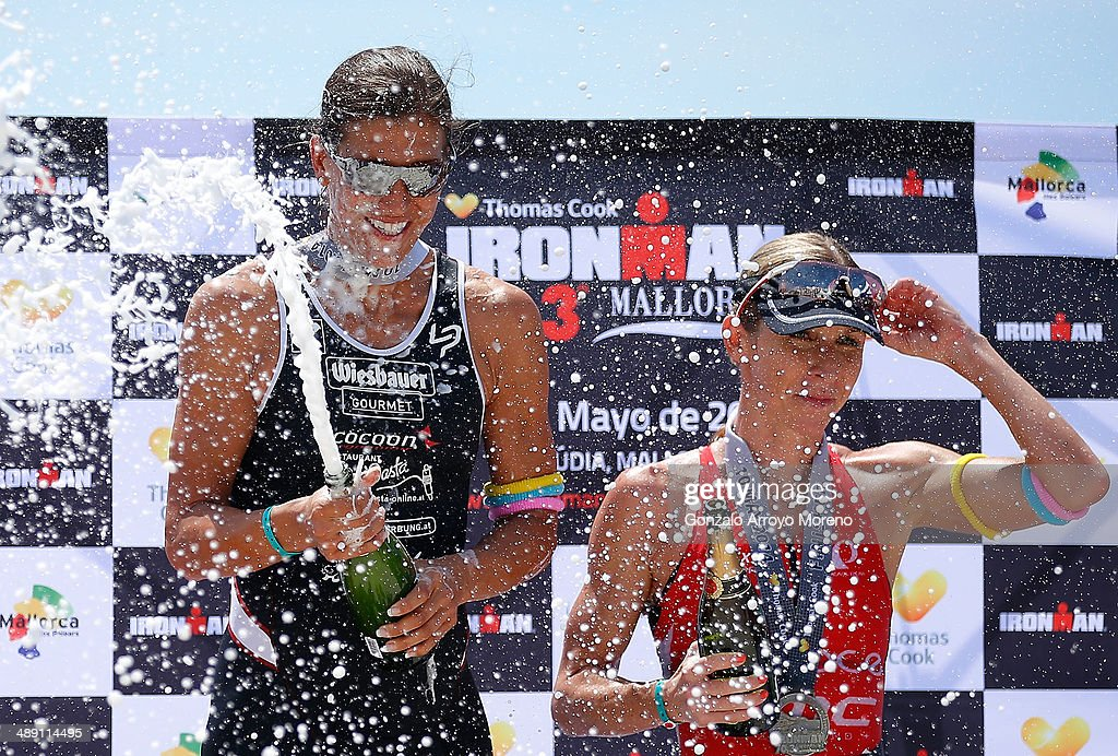 First place winner Lisa Huetthaler (L) sprays champagne as third placed Liz Blatchford looks on following the women's competition in the Ironman 70.3 Mallorca on May 10, 2014 in Mallorca, Spain.