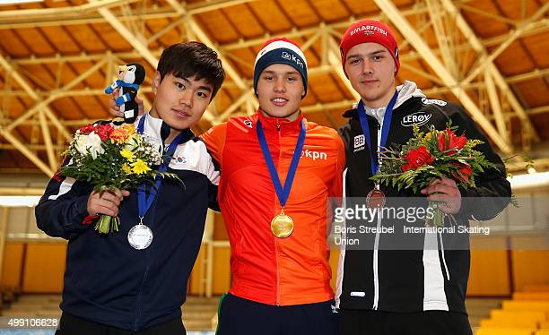 First place winner Marcel Bosker of the Netherlands celebrates on the podium with second place MinSeok Kim of Korea and third place winner Allan Dahl...