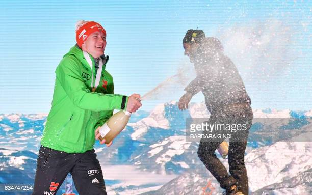 First placed Benedikt Doll of Germany and third placed Martin Fourcade of France spray champagne after Men's 10 km sprint in Hochfilzen Austria on...