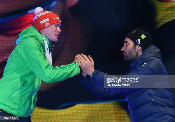 First placed Benedikt Doll of Germany and third placed Martin Fourcade of France shake hands during the medal ceremony during a ceremony after Men's...