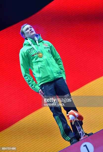 First placed Benedikt Doll of Germany attends a medal ceremony during a ceremony after Men's 10 km sprint in Hochfilzen Austria on February 11 during...