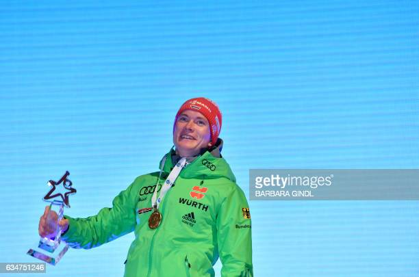 First placed Benedikt Doll of Germany holds a trophy during a ceremony after Men's 10 km sprint in Hochfilzen Austria on February 11 during the...