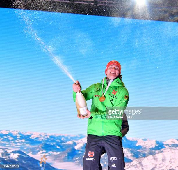 First placed Benedikt Doll of Germany sprays champagne during the medal ceremony during a ceremony after Men's 10 km sprint in Hochfilzen Austria on...