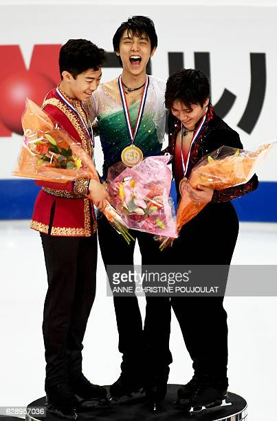 First placed Japanese Yuzuru Hanyu second placed US Nathan Chen and third placed Japan's Shoma Uno pose on the podium with their medals as they...