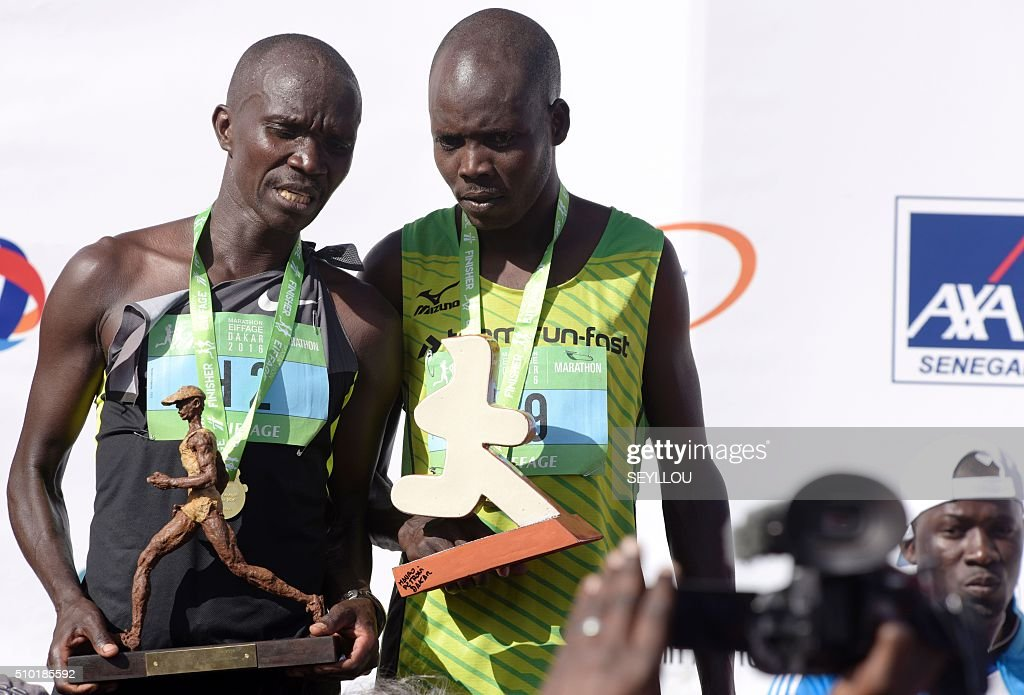 First placed Kenyan athletes Bellor Miningwo Yator (L) speaks with third placed Kiprono Boaz as they pose on the podium after winning the male category of the first ever Dakar International Marathon long 42,195km in 2h 16mm 37s according to official results in Dakar on February 14, 2016. The competition organised by the BTP Eiffage society started on February 13 in front of International Conference Center Abou Diouf (Cicad) on the outskirts of Dakar with different runs of 10 km and will end the day after, February 14, with a marathon. The BTP Eiffage society hosted the event to celebrates its 90 years of presence in Senegal. / AFP / SEYLLOU