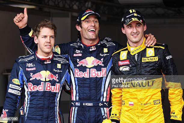 First placed Mark Webber of Australia and Red Bull Racing celebrates in parc ferme with second placed Robert Kubica of Poland and Renault and third...