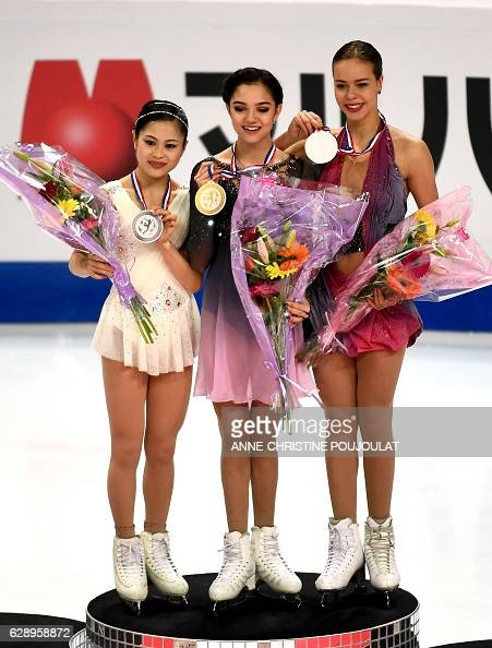 First placed Russian Evgenia Medvedeva second placed Japan's Satoko Miyahara and third placed Russian Anna Pogorilaya pose on the podium with their...