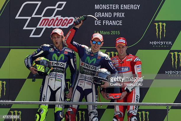 First placed winner Spain's Jorge Lorenzo second placed winner Italy's Valentino Rossi and third placed winner Italy's Andrea Dovizioso celebrate on...
