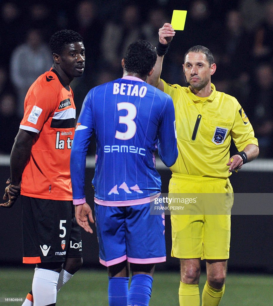 First referee Mikael Lesage (R) gives a yellow card during the French L1 football match Lorient vs Evian on February 16, 2013 at the Moustoir Stadium in Lorient, western France.