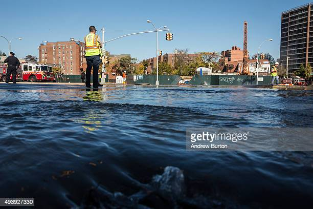A first responder from the New York City Department of Environmental Protection works at the site of a water main break on October 23 2015 in the...