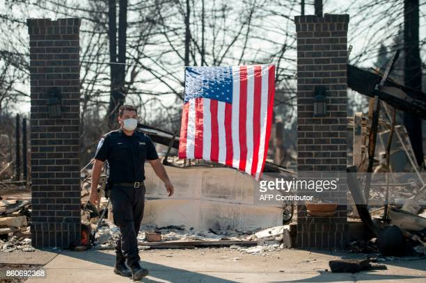 First responder Luis Flores walks out of a burned property in Santa Rosa California on October 12 2017 Hundreds of people are still missing in...