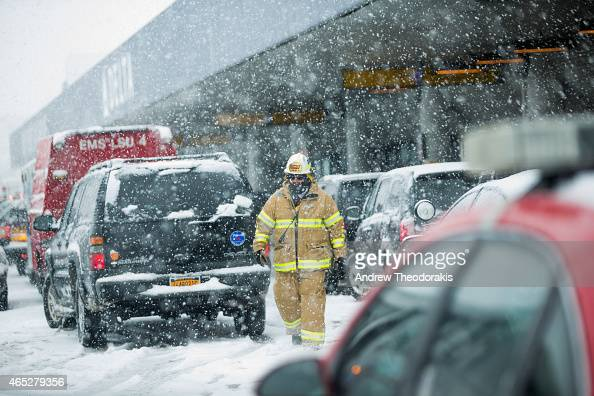 A first responder walks outside the Delta terminal March 5 2015 at LaGuardia Airport in the Queens borough of New York City A Delta jet partially...