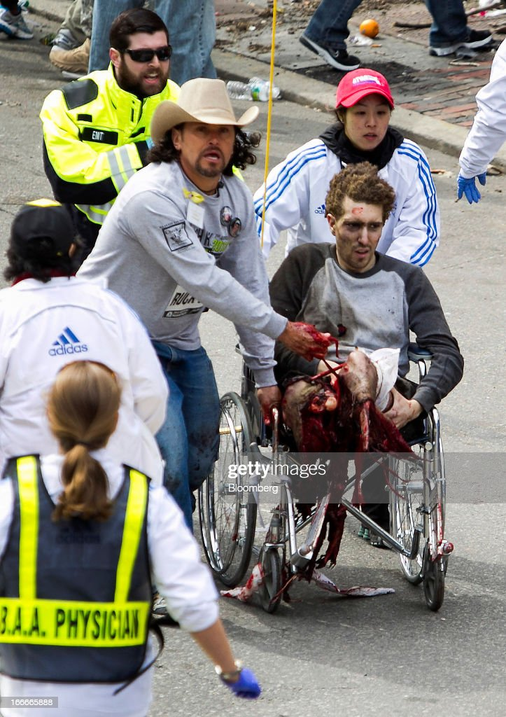 CONTENT** First responders including Carlos Arredondo, in cowboy hat, tend to Jeff Bauman, who was severely wounded after two explosions occurred along the final stretch of the Boston Marathon on Boylston Street in Boston, Massachusetts, U.S., on Monday, April 15, 2013. Two powerful explosions rocked the finish line area of the Boston Marathon near Copley Square and police said many people were injured. Photographer: Kelvin Ma/Bloomberg **EDITORS