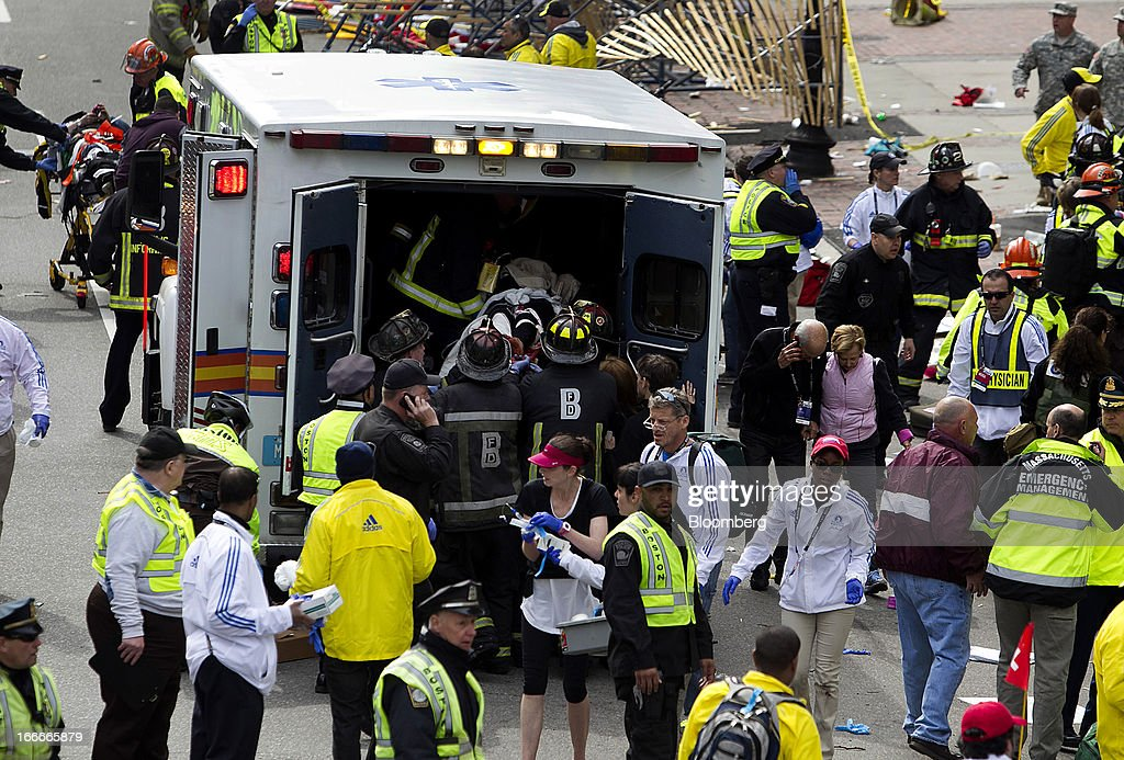 First responders load injured people into an ambulance where two explosions occurred along the final stretch of the Boston Marathon on Boylston Street in Boston, Massachusetts, U.S., on Monday, April 15, 2013. Two powerful explosions rocked the finish line area of the Boston Marathon near Copley Square and police said many people were injured. Photographer: Kelvin Ma/Bloomberg via Getty Images