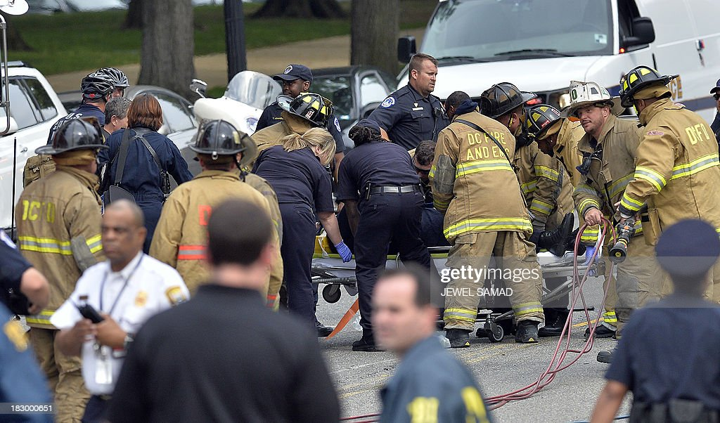 First responders put a police officer on the stretcher after pulling his out of a wrecked police car after shots fired were reported near 2nd Street NW and Constitution Avenue on Capitol Hill in Washington, DC, on October 3, 2013. The US Capitol was placed on security lockdown Thursday after shots were fired outside the complex, senators said. 'Shots fired outside the Capitol. We are in temporary lock down,' Senator Claire McCaskill said on Twitter. Police were seen running within the Capitol building and outside as vehicles swarmed to the scene. AFP Photo/Jewel Samad