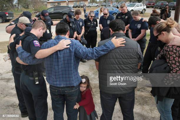 First responders share a prayer following a Veterans Day ceremony outside the Community Center on November 11 2017 in Sutherland Springs Texas The...
