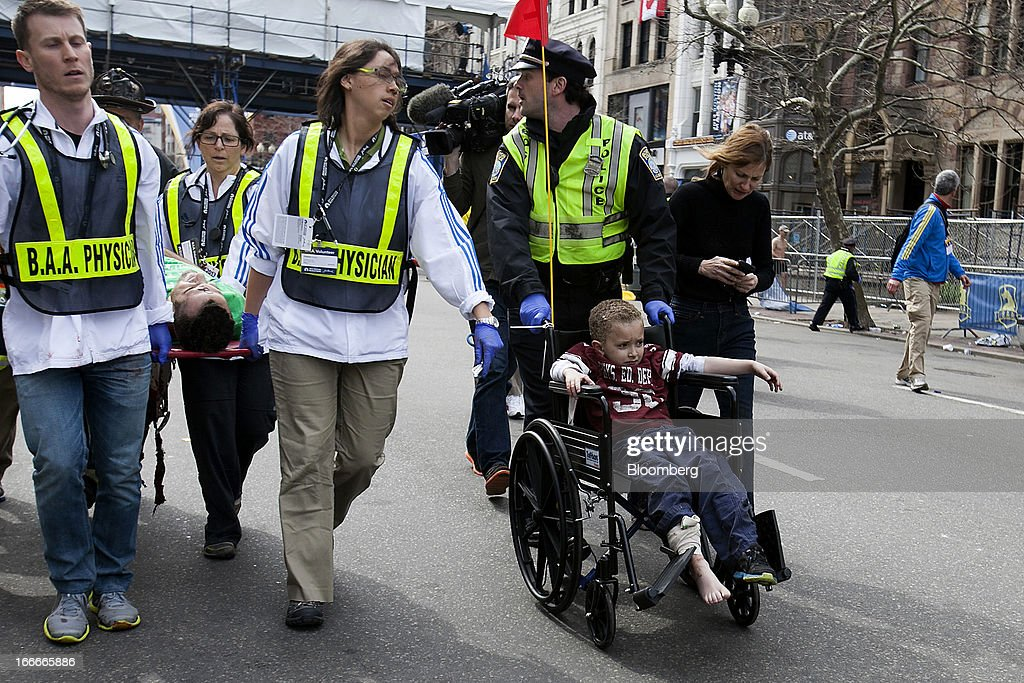 First responders tend to the wounded, including a young boy in a wheelchair, where two explosions occurred along the final stretch of the Boston Marathon on Boylston Street in Boston, Massachusetts, U.S., on Monday, April 15, 2013. Two powerful explosions rocked the finish line area of the Boston Marathon near Copley Square and police said many people were injured. Photographer: Kelvin Ma/Bloomberg via Getty Images