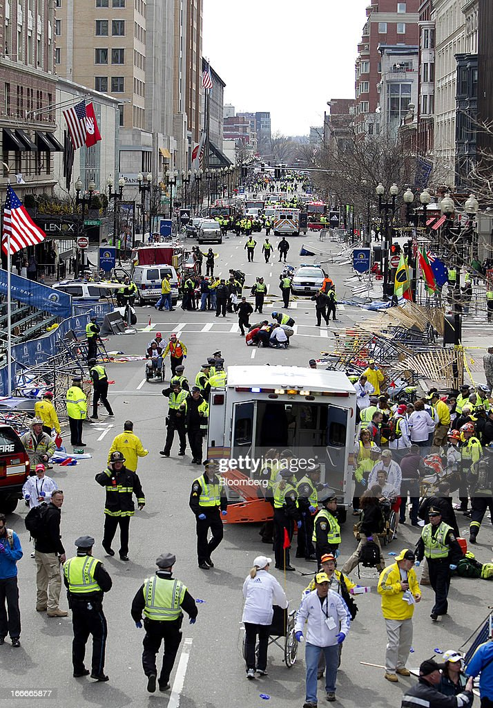 First responders tend to the wounded where two explosions occurred along the final stretch of the Boston Marathon on Boylston Street in Boston, Massachusetts, U.S., on Monday, April 15, 2013. Two powerful explosions rocked the finish line area of the Boston Marathon near Copley Square and police said many people were injured. Photographer: Kelvin Ma/Bloomberg via Getty Images