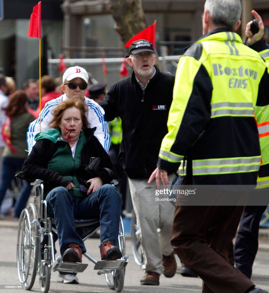 First responders transport an injured woman in a wheelchair where two explosions occurred along the final stretch of the Boston Marathon on Boylston Street in Boston, Massachusetts, U.S., on Monday, April 15, 2013. Two powerful explosions rocked the finish line area of the Boston Marathon near Copley Square and police said many people were injured. Photographer: Kelvin Ma/Bloomberg via Getty Images