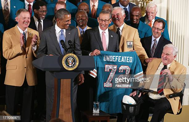 First row US President Barack Obama is presented with a jersey by current team owner Stephen Ross as members of the 1972 Miami Dolphins head coach...