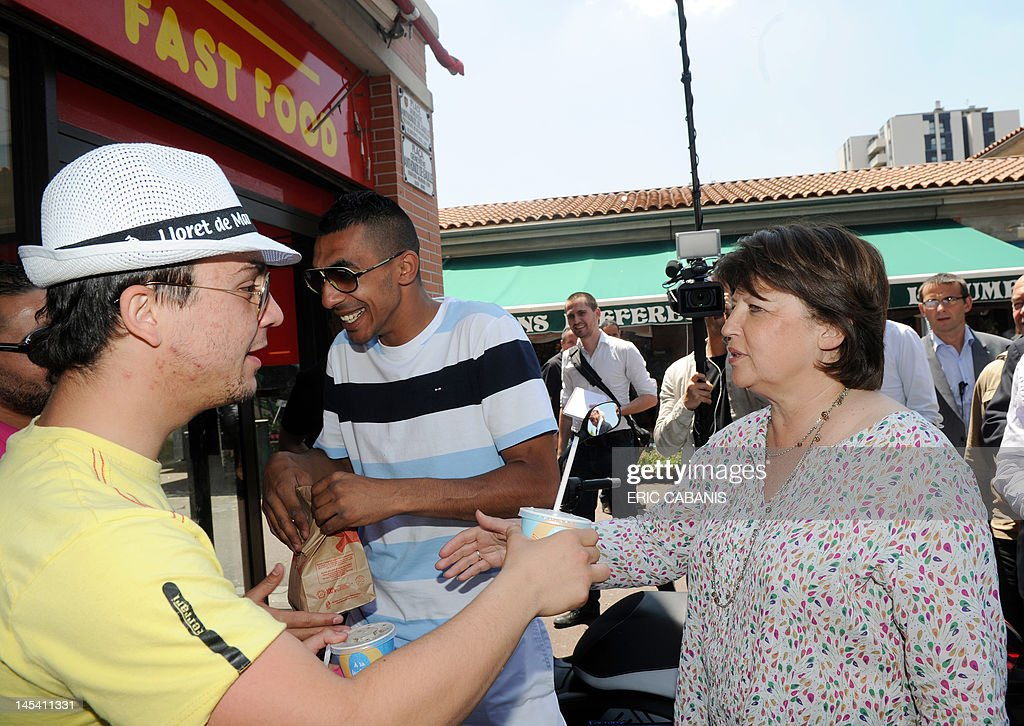 First Secretary of the French Socialist Party Martine Aubry (R), shakes hand with a man as she visits the Bagatelle neighbourhood in Toulouse, southern France when campaining to support Socialist Christophe Borgel in the Haute-Garonne 9th constituency, on May 29, 2012, for the French parliamentary election, next June.
