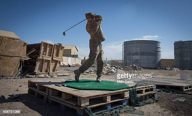 First sergeant Tony Quismundo from the US Army practices his golf on waste ground at Kandahar airfield on November 10 2014 in Kandahar Afghanistan...