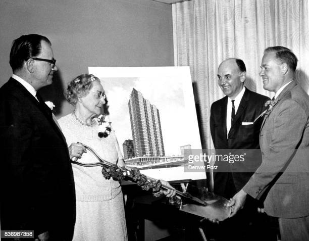 First Step as a new Skyscraper is Born Mrs Elwood Brooks lifts a carnationbedecked shovel she used to start construction of the 4story Brooks Towers...