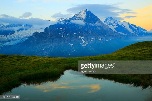 First Swiss Alps: Eiger, mirrored lake above Grindelwald, dramatic sunrise