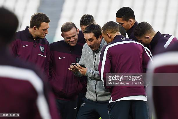 First Team Coach Gary Neville of England laughs with England players including Phil Jones and Wayne Rooney during an England team stadium visit ahead...