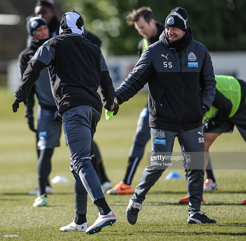 First Team Coach Steve Stone (R) laughs whilst giving Papiss Cisse (L) a bib during a Newcastle United Training session at The Newcastle United Training Centre on March 3, 2015, in Newcastle upon Tyne, England.